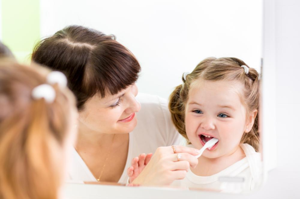 a mom brushes her daughter's teeth | dentist humble tx