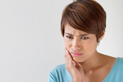 a woman holds her hand to her jaw | root canals humble tx