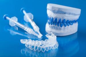 teeth whitening gels and trays sit on top of a blue backdrop | teeth whitening humble tx