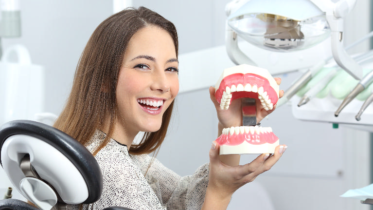 a woman smiles in the dental chair holding a model of teeth | general dentist humble tx
