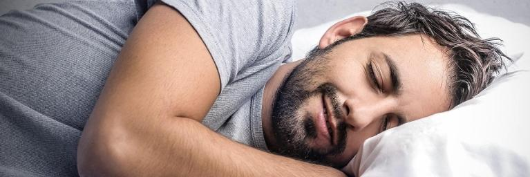 a man lies awake in bed | sleep apnea treatment humble