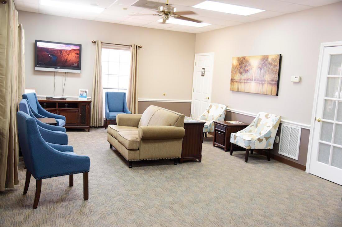 our front-office reception area, featuring a couch, and arm chairs | dentist in humble tx